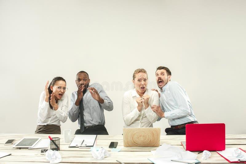 Hombres jovenes y mujeres que se sientan en la oficina y que trabajan en los ordenadores portátiles Concepto de las emociones imagenes de archivo