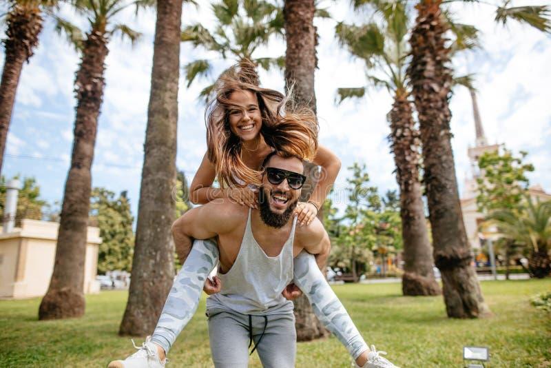 Hombres juguetones juguetones que dan a cuestas paseo a las mujeres en el parque tropical fotos de archivo