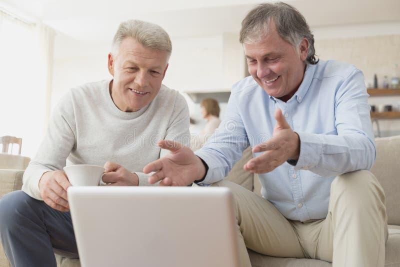 Hombres maduros sonrientes que usan el ordenador portátil mientras que se sienta en casa fotografía de archivo