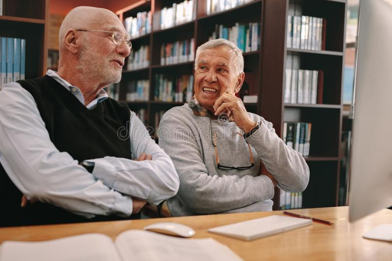 Hombres mayores que se sientan en una sala de clase y hablar imagen de archivo libre de regalías