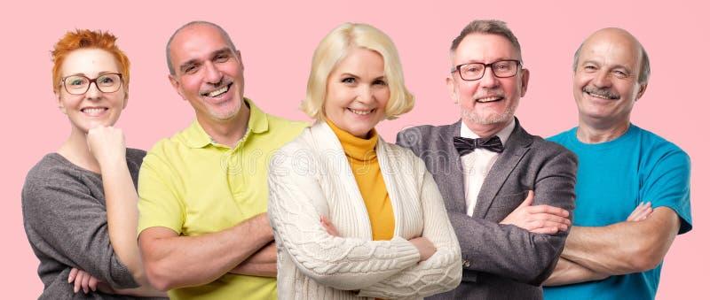 Hombres mayores y mujeres sonrientes confiados que presentan con los brazos doblados fotografía de archivo