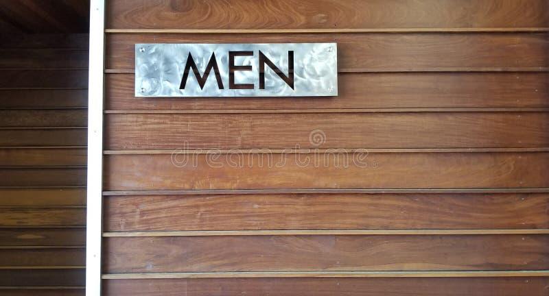 HOMBRES - Muestra de acero inoxidable en la pared de madera natural imagen de archivo libre de regalías