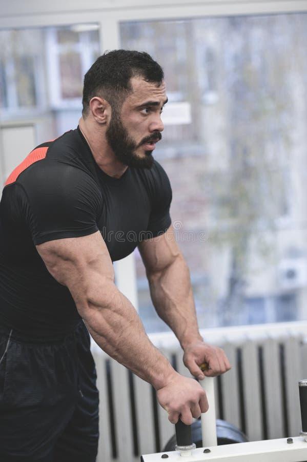 Hombres musculares barbudos y guapos en camiseta negra descansan en el gimnasio durante una pausa de entrenamiento duro imagenes de archivo