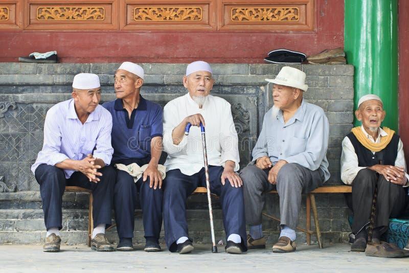Hombres musulmanes de la minoría de Hui en un banco, Yinchuan, China foto de archivo libre de regalías