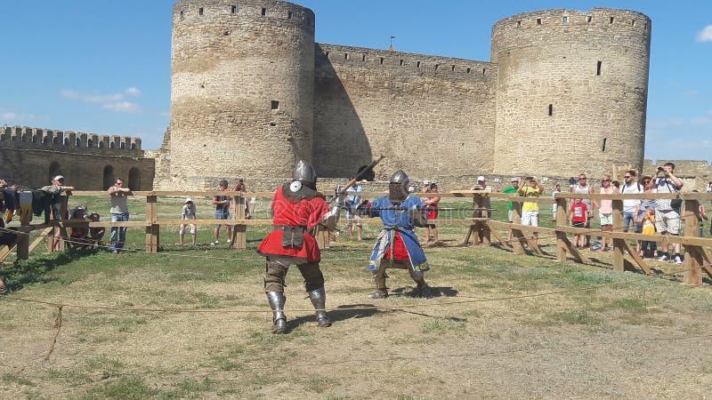 Hombres no identificados en la armadura que demuestra habilidades que luchan durante la reconstrucción del torneo cerca de castil imagen de archivo libre de regalías