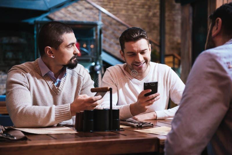 Hombres positivos agradables que sostienen sus smartphones fotografía de archivo