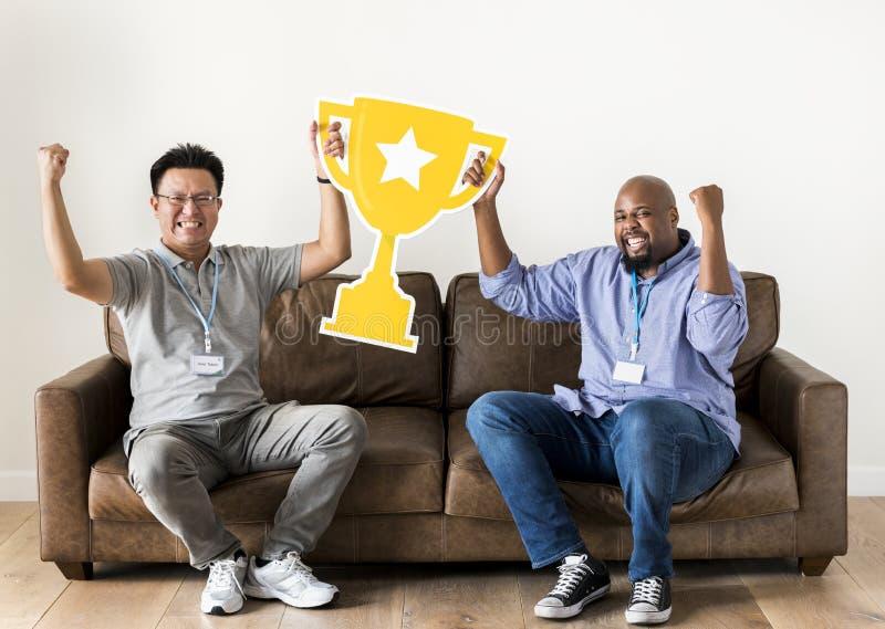 Hombres que celebran éxito con un trofeo foto de archivo libre de regalías