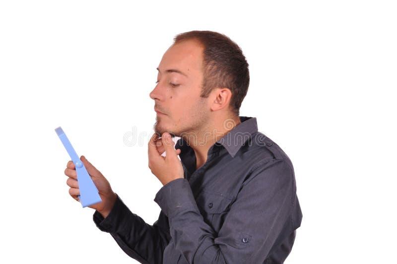 Hombres que comprueban su cara en el espejo fotos de archivo libres de regalías