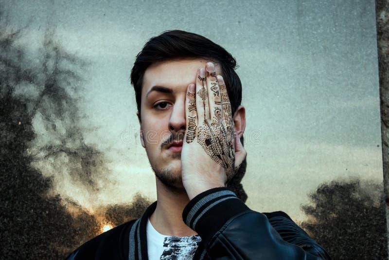 Hombres que cubren el suyo ojo con la mano del tatuaje fotos de archivo libres de regalías