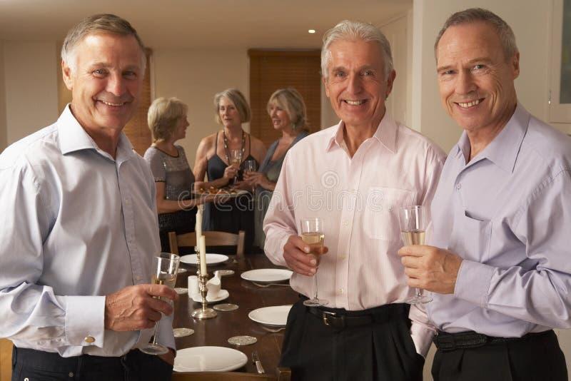 Hombres que disfrutan de Champán en un partido de cena foto de archivo libre de regalías