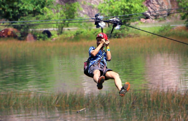Hombres que disfrutan de la cremallera-línea que vuela sobre el bosque en el centro turístico de la colina de Tadom imagenes de archivo