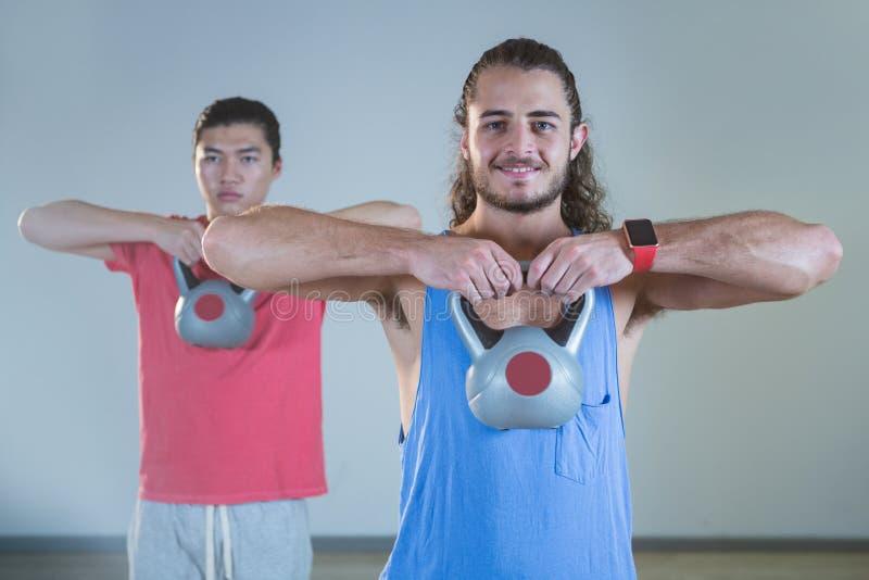 Hombres que ejercitan con el kettlebell imagen de archivo libre de regalías