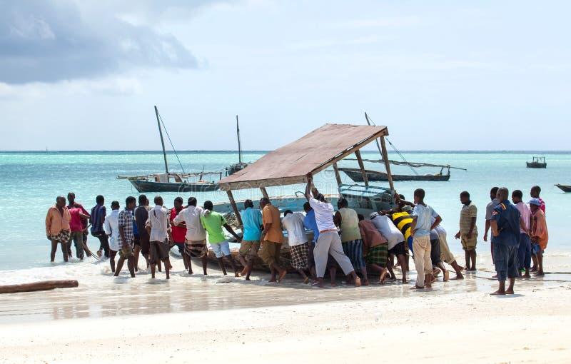 Hombres que empujan el barco de pesca en el mar imagen de archivo