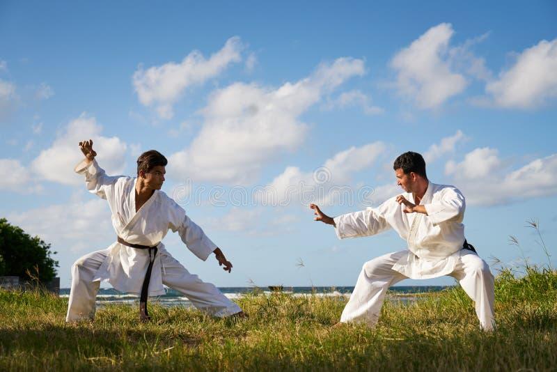 Hombres que golpean luchar con el pie de perforación durante el karate Simulat del deporte del combate imagen de archivo libre de regalías