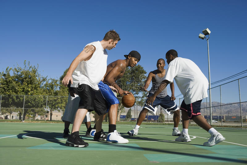 Hombres que juegan a baloncesto en corte foto de archivo