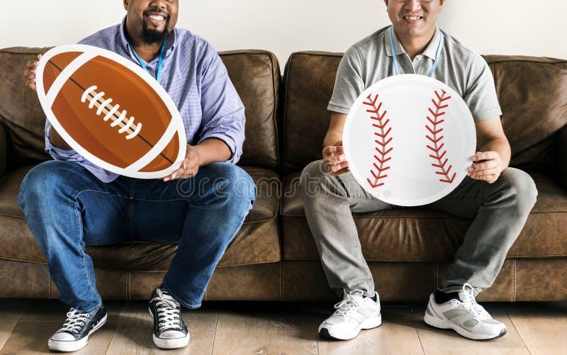 Hombres que llevan a cabo los iconos del béisbol y del rugbi que se sientan en el sofá fotografía de archivo libre de regalías