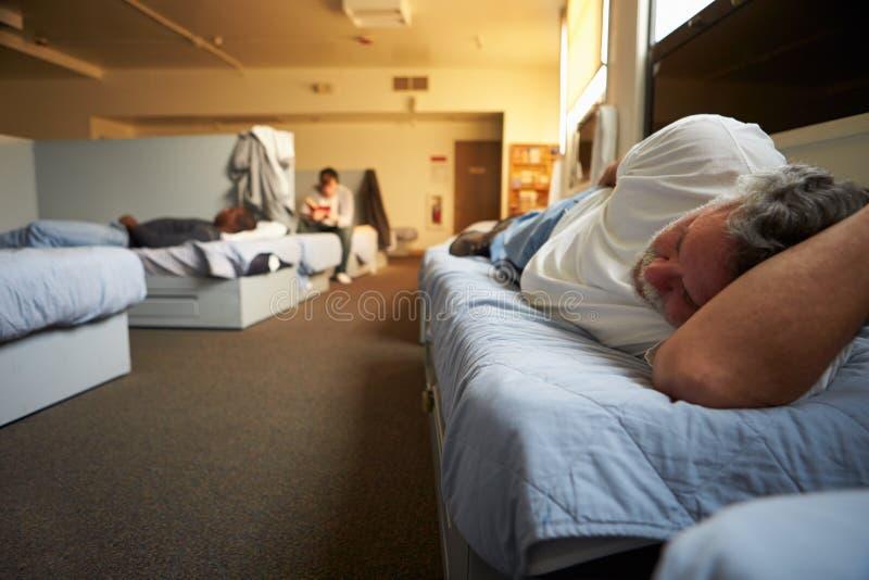Hombres que mienten en camas en refugio para personas sin techo fotos de archivo
