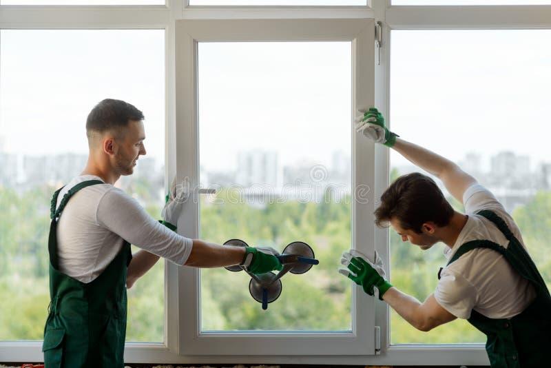 Hombres que montan una sección de la ventana imagenes de archivo