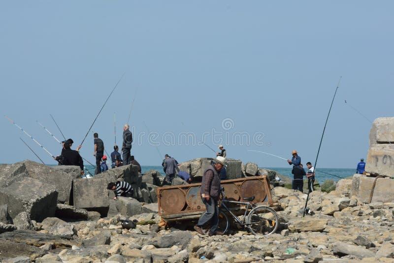 Hombres que pescan de rocas en Sumgait, Azerbaijan foto de archivo libre de regalías