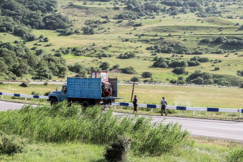 Hombres que pintan la cerca del camino en las montañas de Armenia con un camión azul y una correa eslabonada fotografía de archivo