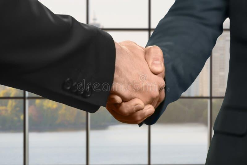 Hombres que sacuden las manos dentro de la oficina fotografía de archivo libre de regalías