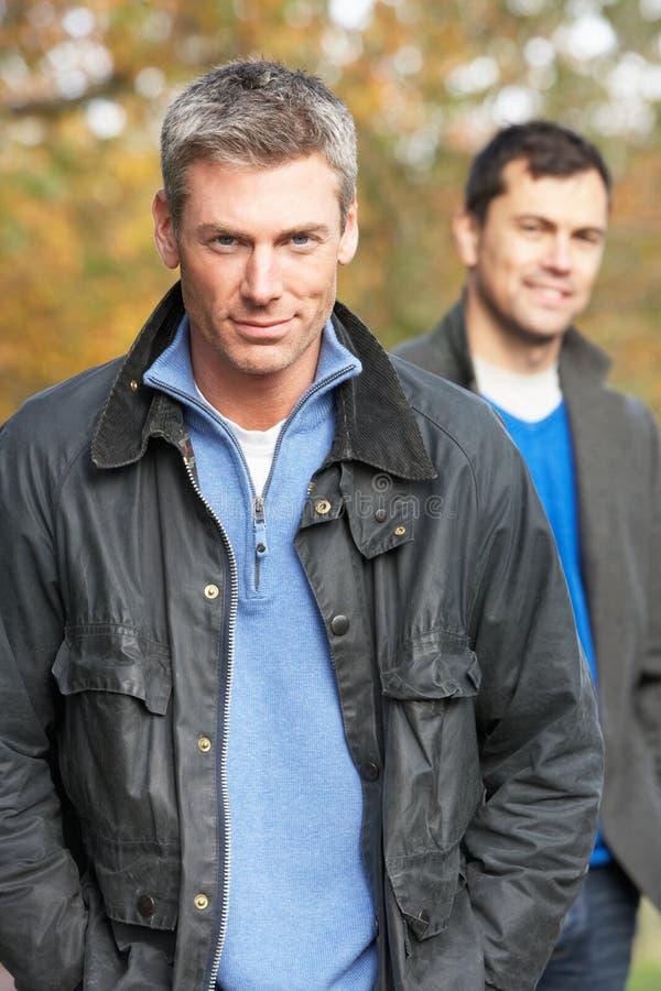 Hombres que se colocan afuera en arbolado del otoño imagen de archivo libre de regalías