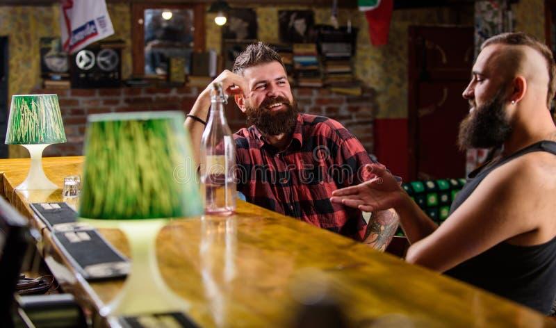Hombres que se relajan en la barra Bebidas fuertes del alcohol Relajaci?n de viernes en barra Amigos que se relajan en barra o pu fotografía de archivo libre de regalías
