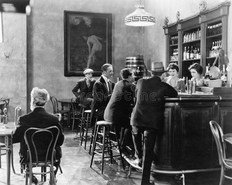 Hombres que se sientan alrededor de un contador en una barra (todas las personas representadas no son vivas más largo y ningún es imágenes de archivo libres de regalías