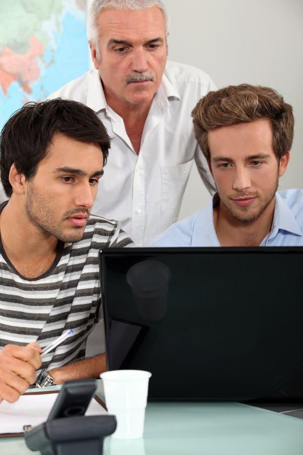 Hombres que se sientan alrededor del ordenador portátil imagen de archivo libre de regalías