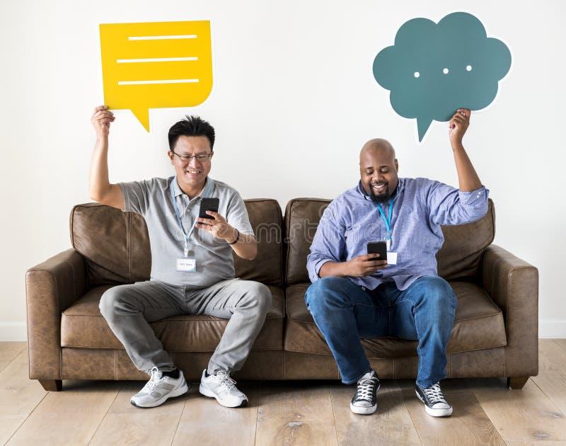 Hombres que sostienen los cuadros de mensaje y que trabajan en móvil foto de archivo