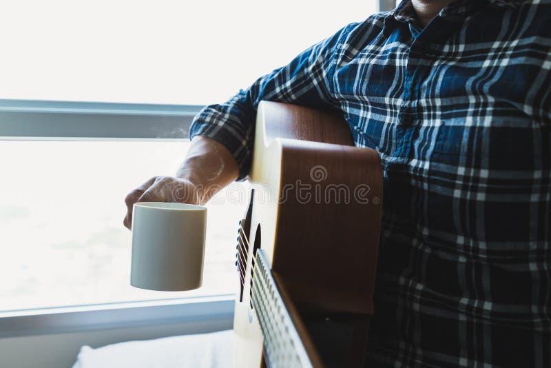 Hombres que sostienen una taza y una guitarra de café fotografía de archivo