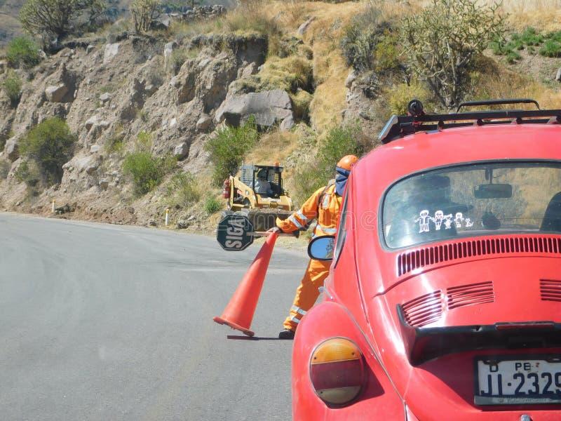 Hombres que trabajan en el camino y la seguridad en carretera imagen de archivo