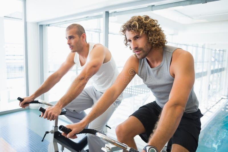 Hombres que trabajan en las bicicletas estáticas en el gimnasio foto de archivo libre de regalías