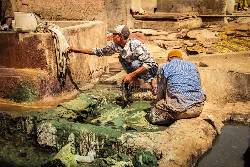 Hombres que trabajan en una curtiduría marrakesh marruecos fotos de archivo