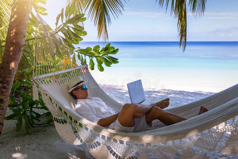 Hombres que trabajan en una playa tropical con su ordenador port?til foto de archivo