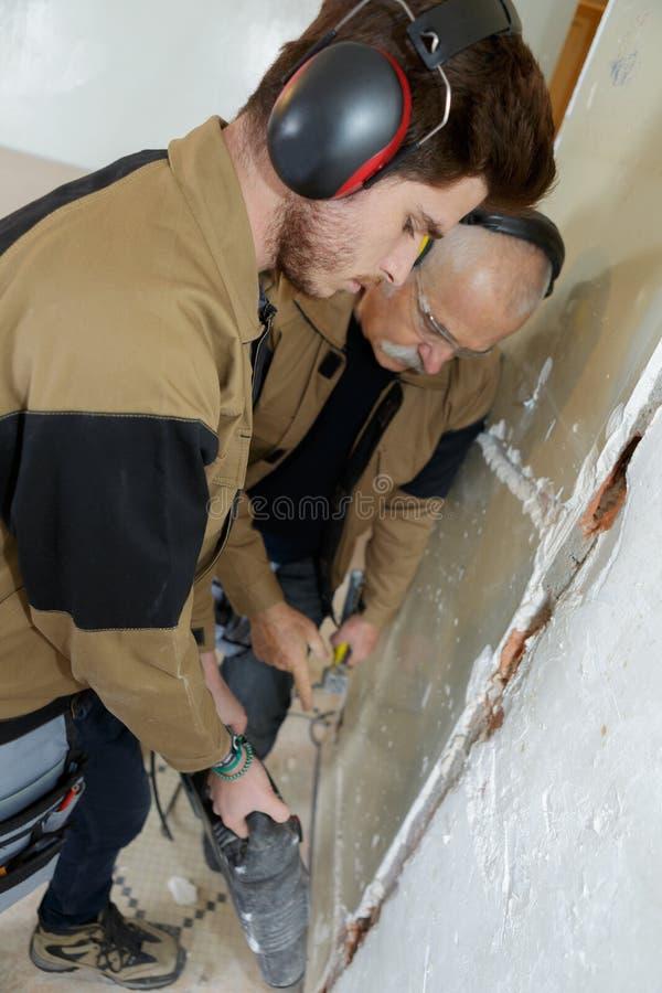 Hombres que usan el taladro de martillo para quitar el yeso de la pared fotografía de archivo libre de regalías