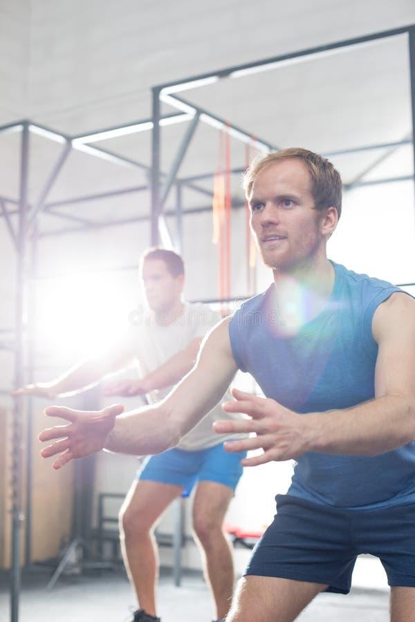 Hombres resueltos que ejercitan en el gimnasio del crossfit foto de archivo
