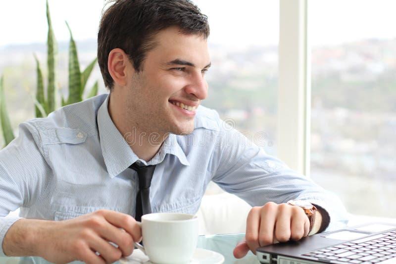 Hombres sonrientes que beben té y mirada en la computadora portátil imágenes de archivo libres de regalías