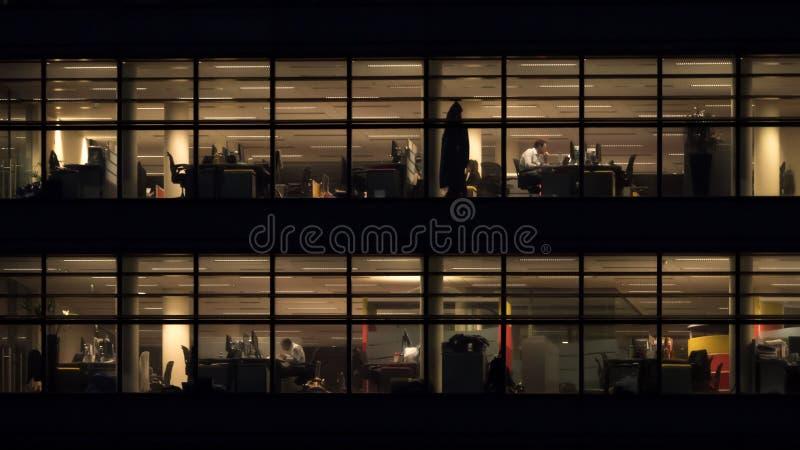 Hombres todav?a que trabajan en el edificio de oficinas en la noche fotografía de archivo libre de regalías