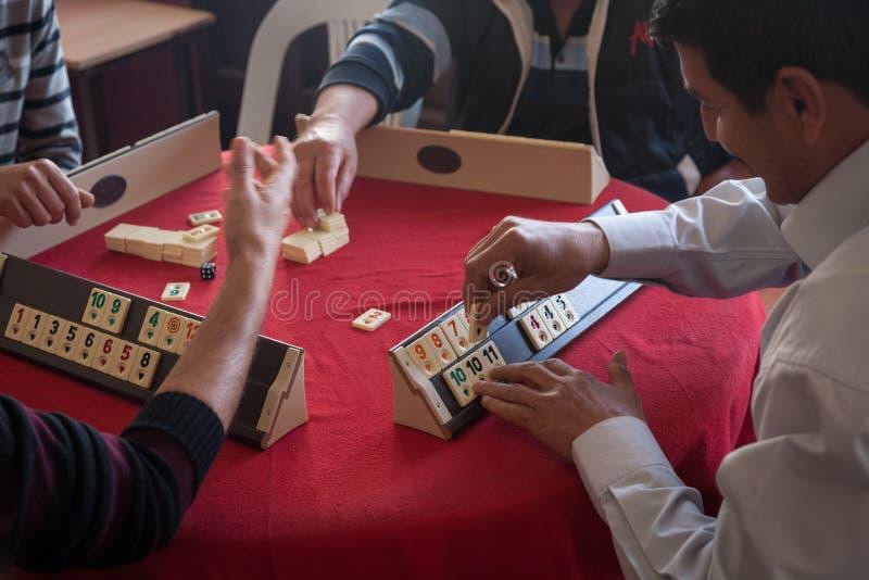 Hombres turcos locales que juegan mismo al juego Okey de tabla, o rummikub, adentro fotos de archivo