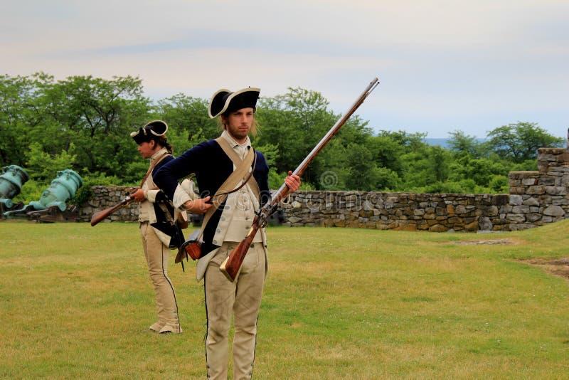 Hombres vestidos como soldados, uso de nuevo promulgación del mosquete, fuerte Ticonderoga, Nueva York, 2014 foto de archivo libre de regalías