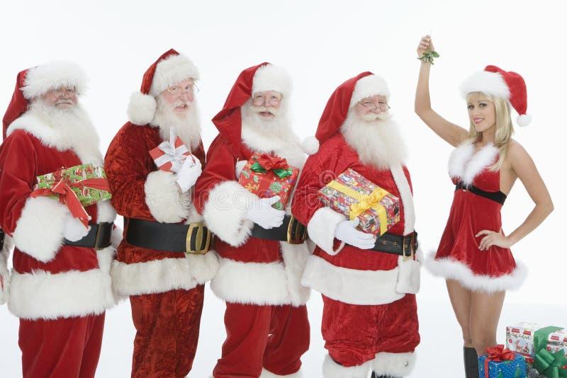 Hombres vestidos en Santa Claus Outfits With Mrs. Claus Holding Mistletoe fotos de archivo libres de regalías
