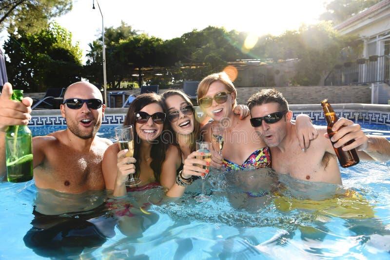 Hombres y mujeres atractivos felices en el bikini que tiene baño en la cerveza de consumición de la piscina del centro turístico  imágenes de archivo libres de regalías