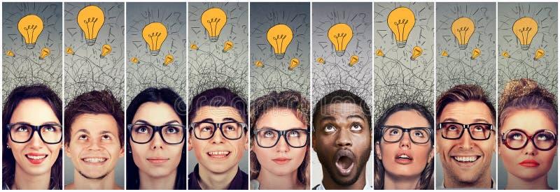 Hombres y mujeres del grupo de personas con muchas bombillas de las ideas sobre la cabeza que mira para arriba fotos de archivo libres de regalías