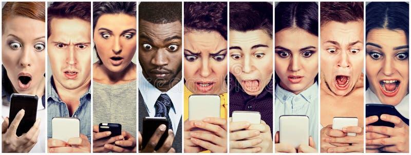 Hombres y mujeres del grupo de personas que miran chocados el teléfono móvil fotos de archivo