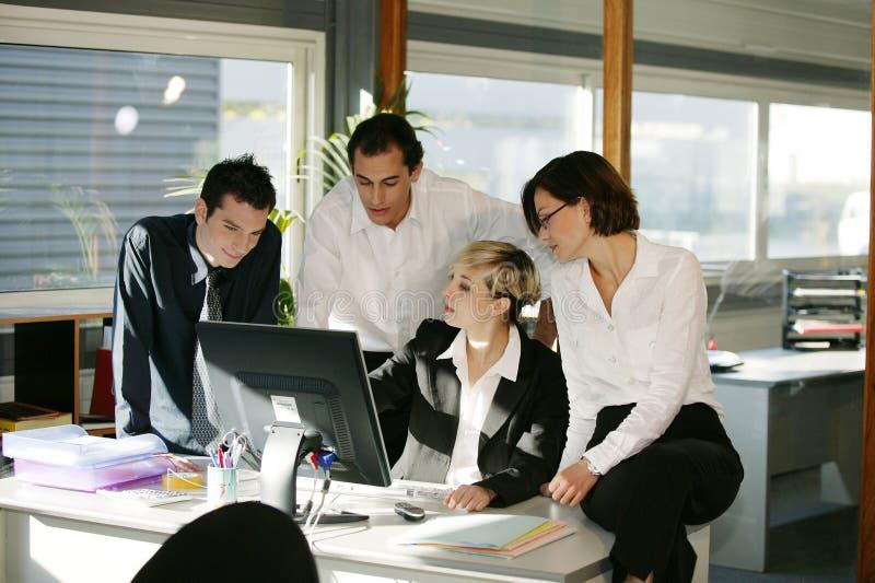 Hombres y mujeres en el escritorio con el ordenador imagen de archivo libre de regalías
