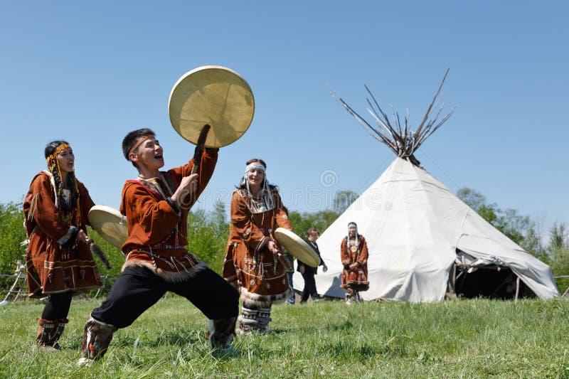 Hombres y mujeres que bailan con una pandereta en la hierba en un yaranga del fondo Kamchatka, Rusia imagen de archivo libre de regalías