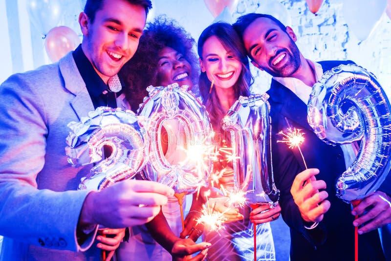 Hombres y mujeres que celebran el Año Nuevo 2019 imagenes de archivo