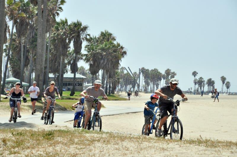 Hombres y mujeres que montan en los tándems en la playa de Venecia fotografía de archivo