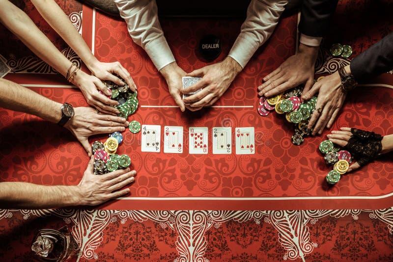 Hombres y mujeres que sostienen las fichas de póker en casino fotografía de archivo